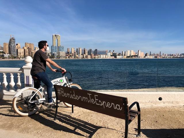 Banco de #BenidormTeEspera al final del Paseo de Poniente, en la zona de La Cala en Benidorm. Se ve el skyline de la ciudad, el mar con un color azul intenso, el cielo azul despejado, y un chico con una bici eléctrica admirando las vistas.