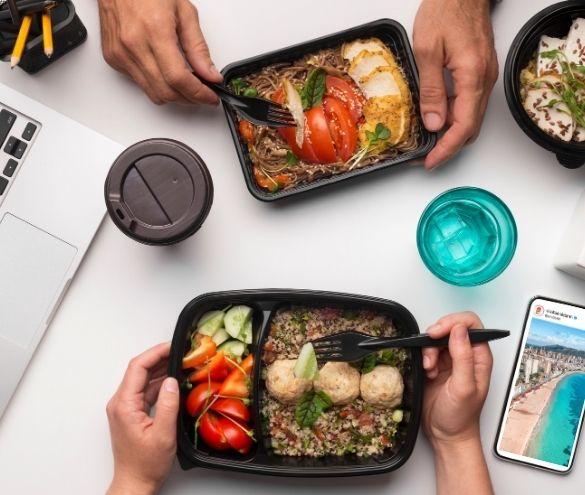 Dos platos de comida preparados en tuppers para llevar, donde se ven verduras, pollo y arroz. Se ven dos pares de manos que van a comerse la comida, y alrededor el móvil, bebidas y un ordenador.