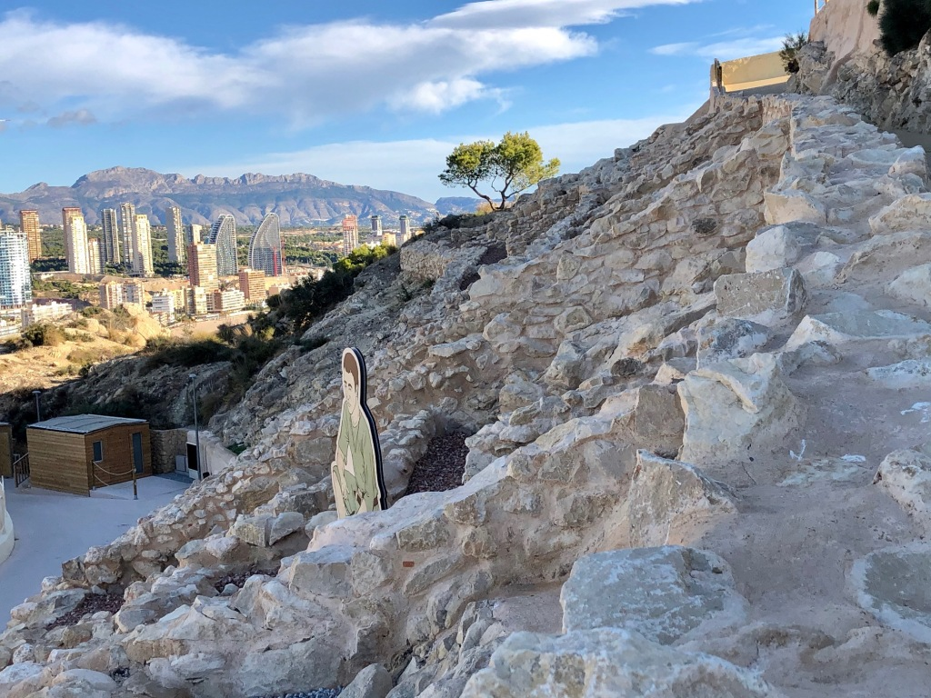Castellum Tossal de La Cala, where you can see some stones from the ancient roman site. In the background you can see Benidorm's skyline under a blue sky.
