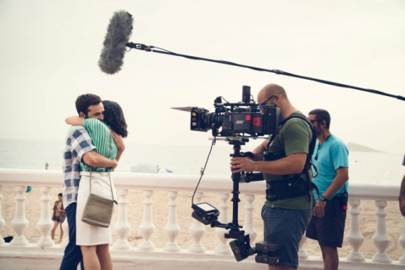 Rodaje de la serie 'Cuéntame cómo pasó', donde se ve dos actores abrazándose. Ella lleva una blusa verde a rayas y una falda blanca; y él una camisa a cuadros blanco y azul y unos vaqueros. Además se ve el equipo de rodaje, con micros y una cámara grabando la escena. De fondo se ve la playa y la Isla de Benidorm.