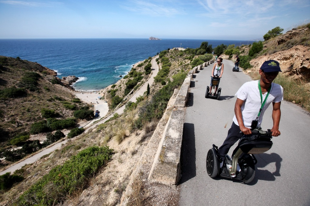 Group of people on a segway tour through Serra Gelada Natural Park. In the background you can see the Benidorm Island in a deep blue sea. You can also see the Tio Ximo cove surrounded by nature.