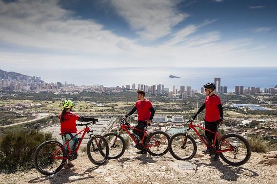Tres personas que han parado a descansar en una ruta por la montaña en bicicleta. En el fondo se ven muchas zonas verdes y seguido el skyline de Benidorm, el cielo azul con algunas nubes, y el mar con la Isla de Benidorm en el centro.