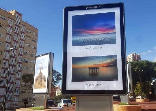 Espacio de arte urbano en Els Tolls, Benidorm. Se ven diferentes fotografías de diferentes artistas expuestas en mupis (soporte de publicidad exterior). Se ve en primer plano dos fotografías de playas al atardecer con los colores azul, naranja y rosa,, y a la izquierda otro mupi con unas jirafas.