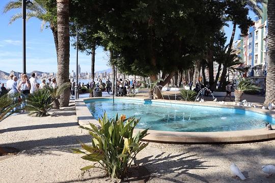 Parque de Elche en Benidorm, ubicado al lado de la Playa de Poniente, donde se ve la fuente con agua de color azul claro y las palmeras verdes que la rodean.