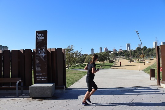 Foietes Park in benidorm. You can see a girl running in the entrance of the park, and in the background you can see the city's skyline.