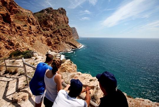 Parque Natural de la Sierra Helada, donde se ve a cuatro personas de espaldas admirando los alto acantilados de color marrón y el mar de un azul intenso que brilla gracias a los rayos de sol.