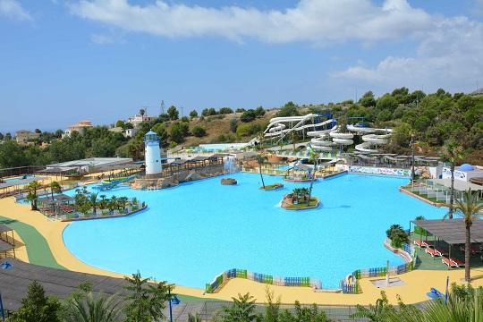 Parque acuático Aqua Natura. Se ve un plano general del parque, donde se distinguen una gran piscina, varios árboles alrededor, y muchos toboganes blancos al fondo.