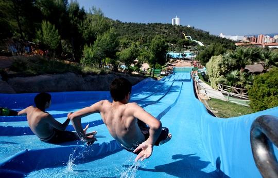 Parque acuático Aqualandia Benidorm. Se ve un tobogán azul con 5 carriles y con pequeños saltos en la bajada, todos ellos ocupados. Está rodeado de árboles, y al fondo se ven unos toboganes de colores.