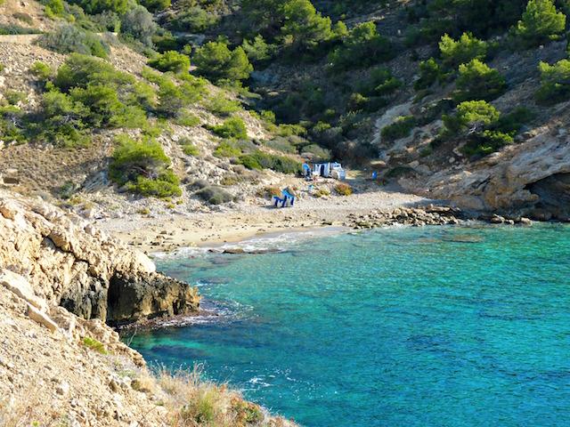 Cala de la Almadraba en Benidotm. Se ven varios arbustos y rocas, y algunas hamacas apiladas. El agua es color azul turquesa.