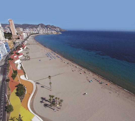 Playa de Poniente en Benidorm. Se ve el paseo de colores rojo naranja y amarillo, conjuntos de palmeras repartidos por la playa, y el skyline de Benidorm a la izquierda.