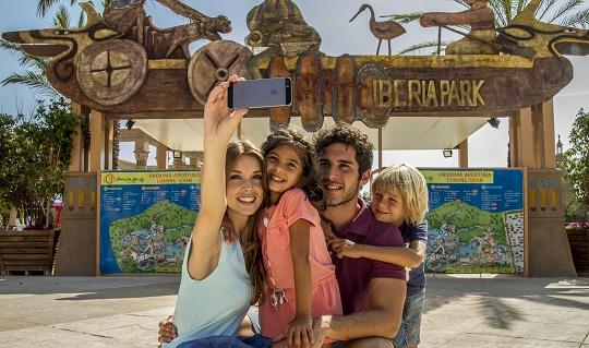 Foto de la entrada de Iberia Park en Benidorm. Sale una familia, de un padre, una madre, un niño y una niña, que están haciéndose una foto. La entrada tiene un plano del parque de gran tamaño, y una decoración antigua.