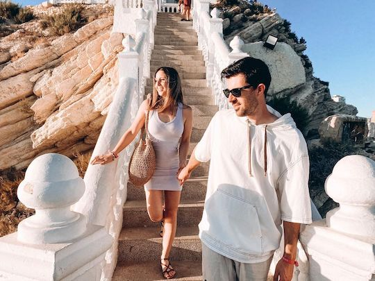Una pareja de mujer y hombre adultos, bajando las escaleras del Castell de Benidorm que llevan a su mirador. Las barandillas son blancas, y las escaleras se encuentran entre rocas que tienen forma plana y están orientadas en diagonal hacia abajo a la izquierda. La chica lleva un vestido corto ceñido violeta, y el hombre lleva una camiseta blanca. Están cogidos de la mano mientras miran sonrientes hacia su derecha.