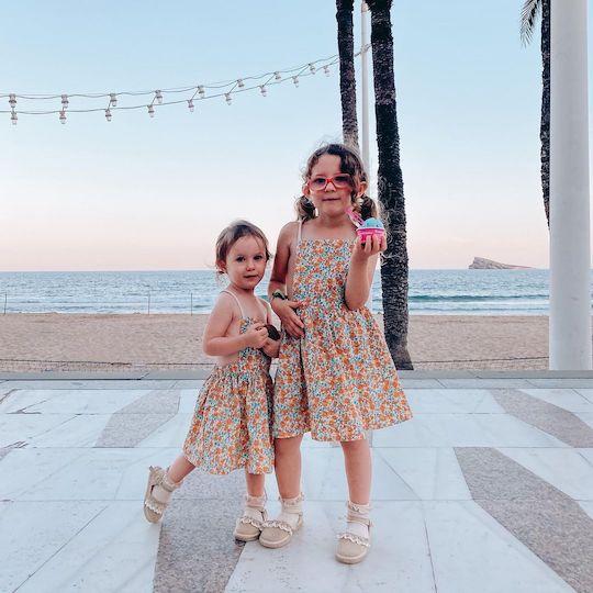 Dos niñas de 4 y 2 años,que ambas llevan el mismo vestido de flores en colores verde y naranja. Se encuentran en el paseo de la playa de Levante en Benidorm al atardecer, y de fondo se ve la playa vacía, el mar mediterráneo tranquilo bajo un cielo despejados con los colores azul y rosa, y la isla de Benidorm.