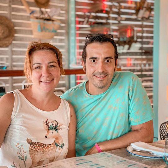 Una mujer y un hombre adultos mirando a la cámara sonrientes sentados en un restaurante que está decorado muy playero, con sombreros de paja en las paredes. El padre lleva una camiseta azul turquesa, y la madre una camiseta blanca con el dibujo de un ciervo.