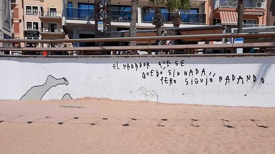 Mural 'El Nadador' en la Playa de Levante de Benidorm, que se encuentra en la pared que separa el paseo de la arena. El fondo es blanco, a la izquierda se ven unos pies hacia arriba, como si estuvieran sumergiéndose en la arena, delineados en negro y rellenados en gris. A la derecha se ve un texto que lee: El nadador que se quedó sin nada, pero siguió nadando.