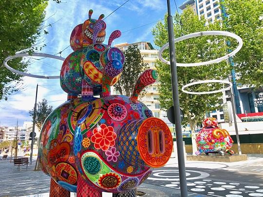 Avenida del Mediterráneo en Benidorm. Se ve en primer plano una de las esculturas de la exposición Galaxia Hung, que son tres cerdos uno encima de otro, siendo el de abajo el más grande y el de arriba el más pequeño. Tienen varios dibujos pintados en ellos como flores, mandalas, letras asiáticas, corazones, etc. en varios colores donde predominan el rojo, rosa, lila, amarillo, azul y verde. Al fondo, al otro lado de la calle, se ve otra de las esculturas que es un carnero grande con otro pequeño encima, con muchos dibujos indistinguibles en los colores rojo, rosa, verde y azul principalmente, y los cuernos de ambos son dorados. Alrededor de las esculturas hay árboles, edificios, y varias luces con forma de circunferencia encima.