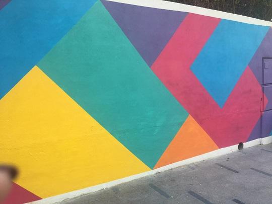 Mural en Calle Herrerías que son varias rayas en diagonal hacia izquierda y derecha, que forman cuadrados de diferentes tamaños. Los cuadrados tienen varios colores, como azul oscuro, amarillo, verde turquesa, rosa, naranja y lila.