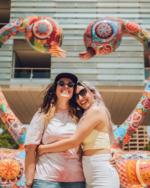 Dos chicas abrazadas, sonrientes y vesrtidas con ropa veraniega, delante de una escultura de Galaxia Hung, que son dos cisnes llenos de pequeños dibujos y colores como rosa, naranja, rojo, amarillo, verde y azul.