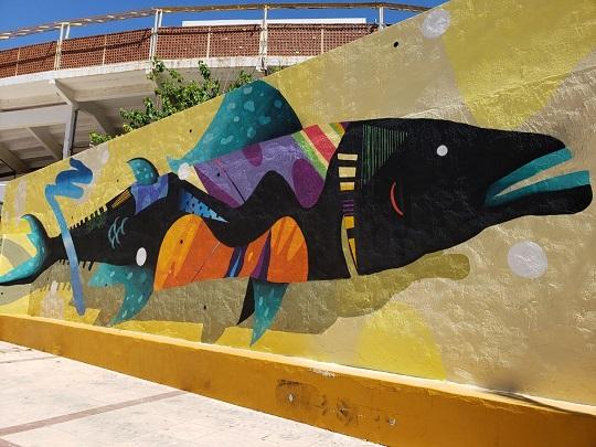 Mural muy grande un pez sobre un fondo negro. El pez tiene la cabeza negra, con los labios, las aletas de arriba, de abajo y de la cola en color azul turquesa con manchas blancas. El resto del cuerpo está formado por diferentes formas como ondas, triángulos y lunares, en los colores lila, naranja y azul claro. Está pintado sobre un fondo con tonos amarillos.
