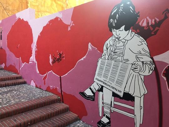 Mural de la Calle de los Gatos en Benidorm. A la izquierda se ven tres amapolas grandes pintadas sobre un fondo rosa y blanco. A la derecha, pintada en blanco y negro, se ve una niña sentada en una silla, con una pierna encima de la otra, leyendo un periódico. Tiene el pelo negro y corto, sin llegar a los hombros, y lleva un vestido de manga larga y de falda corta.