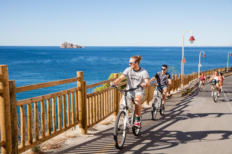 Varias personas manejando bici eléctrica por Sierra Helada en Benidorm, se aprecia el mar azul, la Isla de Benidorm detrás bajo un cielo celeste brillante.